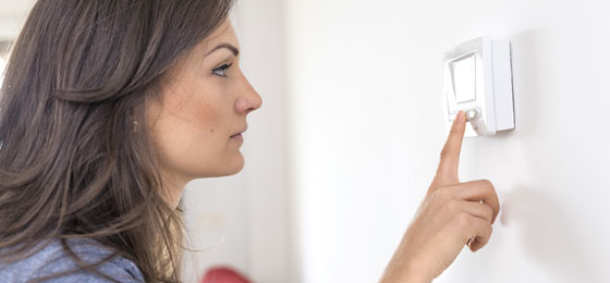 This picture shows a woman adjusting a thermostat.