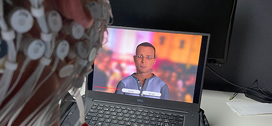 This image shows a subject with electrodes attached to their head watching a character on a computer screen.