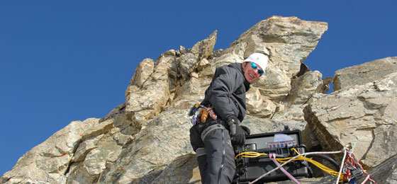 This picture shows a researcher with his instruments in the mountains. ©  PermaSense Project